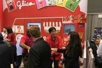 Ezaki Glico USA President Akitoshi Oku, pictured center shaking hands with a woman, at the Sweets and Snacks Expo 2016 in Chicago last month.